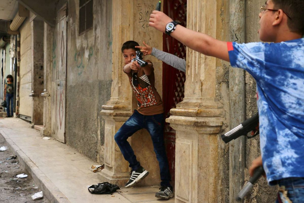 Syrian children play on a street with plastic toys guns in a rebel-held district of the northern city of Aleppo on July 6 during celebrations for Eid al-Fitr, which marks the end of the Muslim holy fasting month of Ramadan.