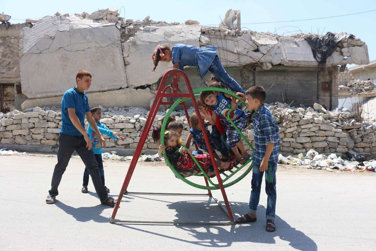 Syrian children play on a swing in front of a damaged building in rebel-held side of Aleppo on July 6 during celebrations for Eid al-Fitr, which marks the end of the Muslim holy fasting month of Ramadan.