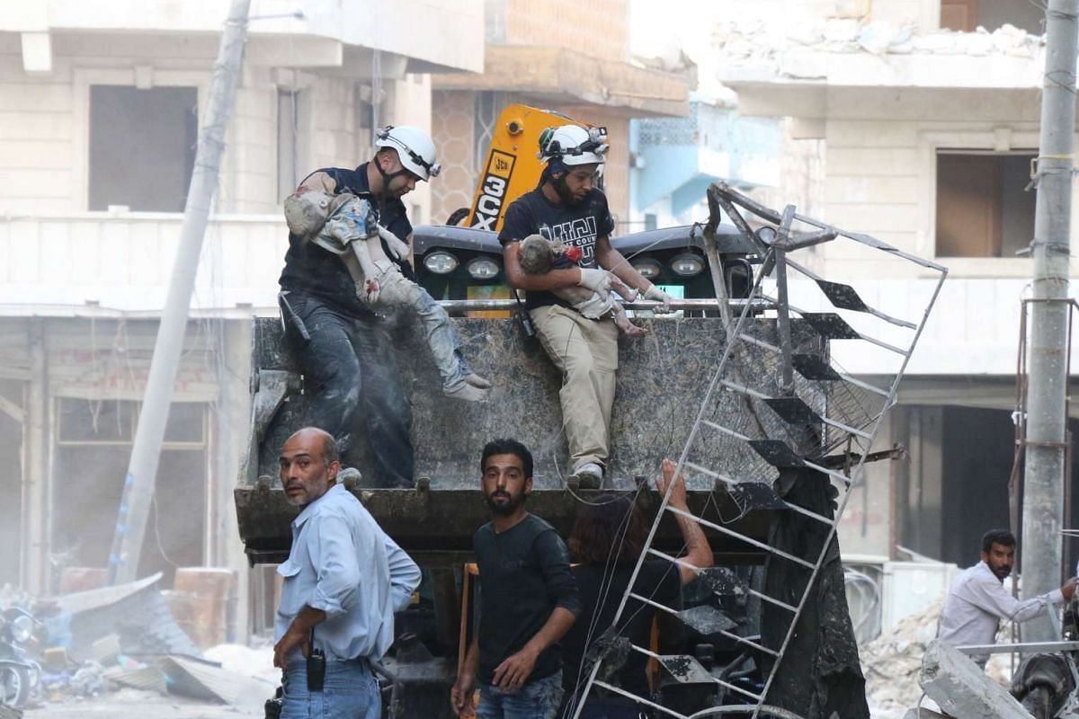 Syrian emergency personnel remove bodies of children from the rubble of a building damaged by air strikes on July 7 in Aleppo's rebel-held neighbourhood of Tariq al-Bab.