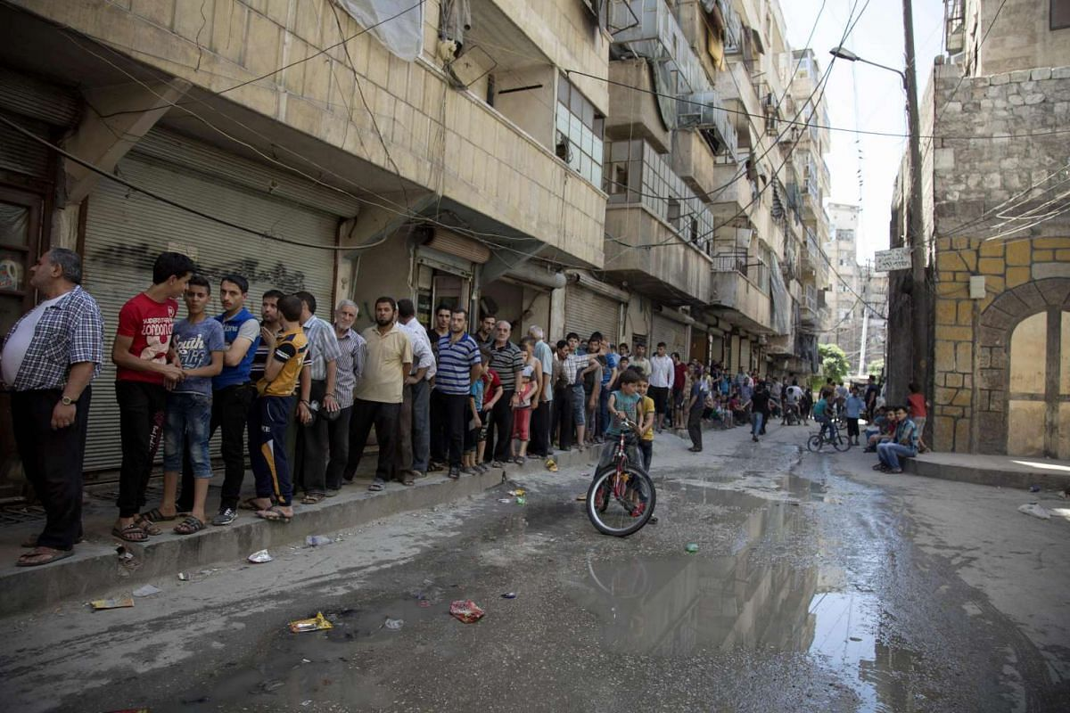 Syrians queue to buy bread in a rebel-held neighbourhood in the northern city of Aleppo on July 12.