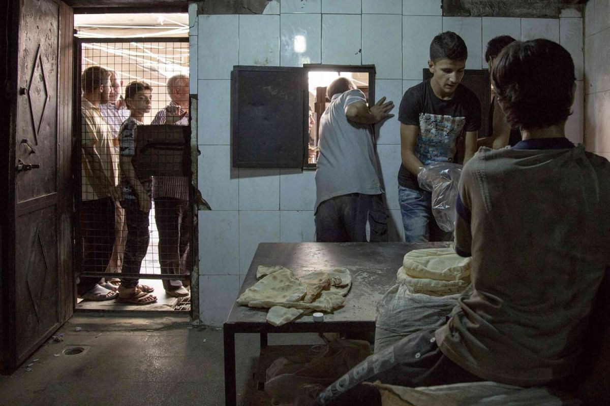 Syrian bakers pack portions of bread as people queue outside a bakery in a rebel-held neighbourhood in the northern city of Aleppo on July 12.