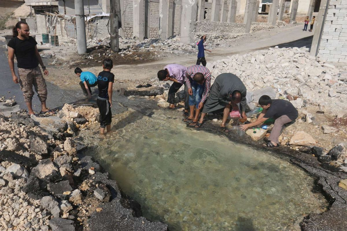 Residents cool down with water from a water pipe damaged by shelling in the rebel-held neighbourhood of Sheikh Saeed, in Aleppo, Syria, on Aug 20.