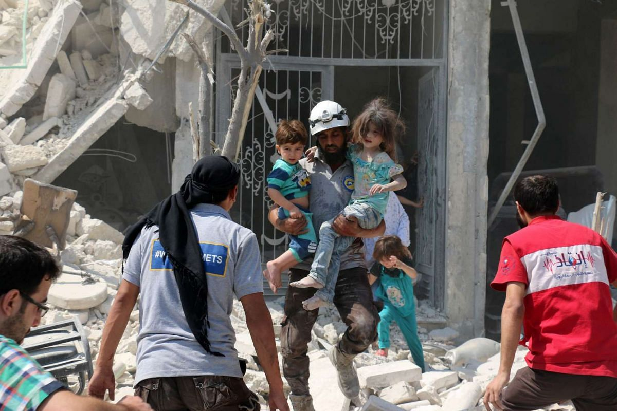 A Syrian rescue worker carries children in the Maadi district of eastern Aleppo after regime aircrafts reportedly dropped explosive-packed barrel bombs on Aug 27.