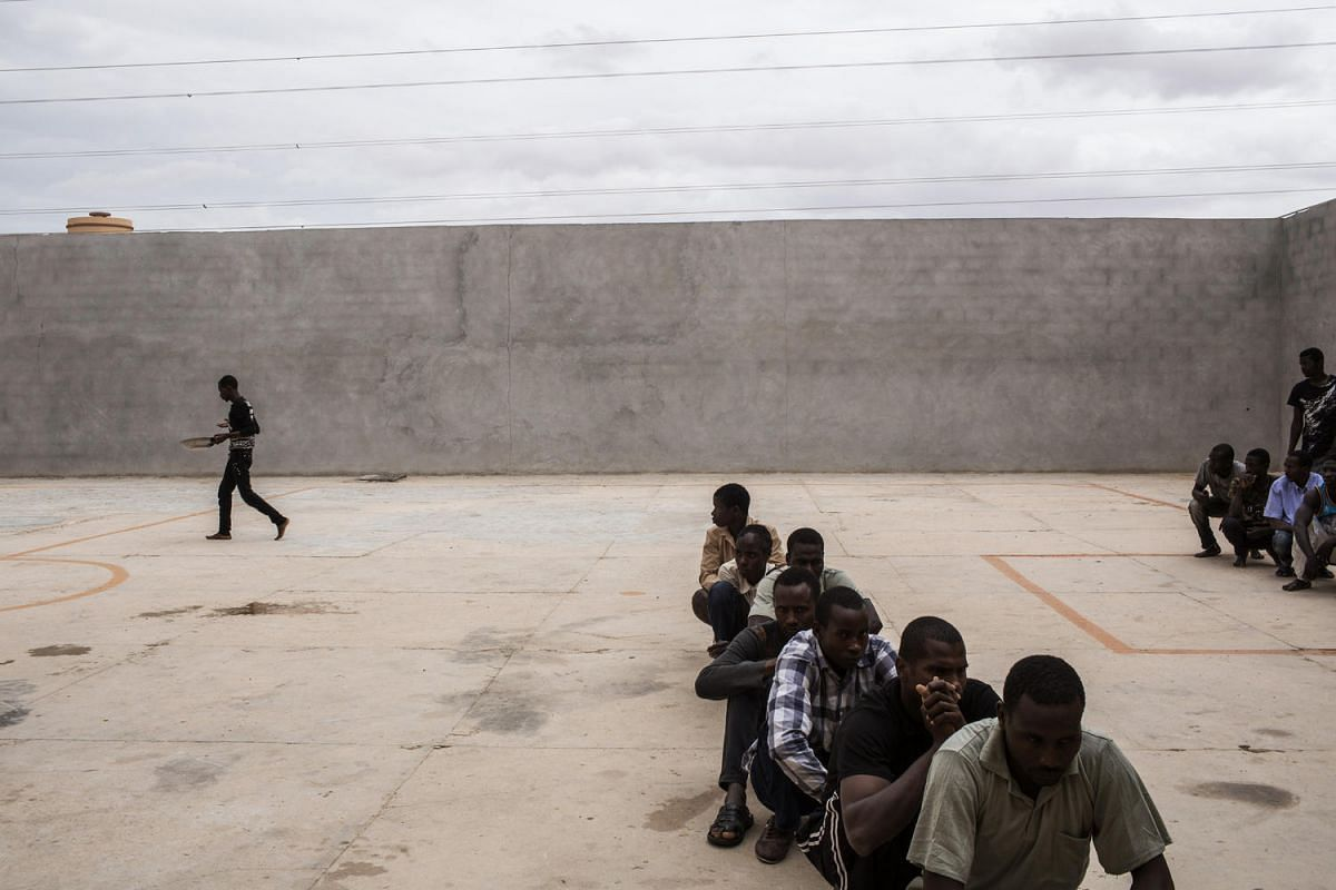 African migrants have their lunch break in the courtyard of Libya's Karareem detention centre near Misrata, a town half-way between Sirte and Tripoli on Sept 25, 2016.