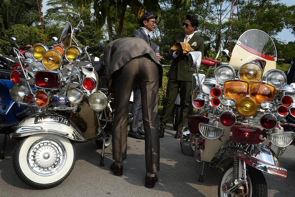 Participants of the 2016 Distinguished Gentlemen's Ride tend to their vintage Vespa scooters at the Dempsey Road pitstop on Sept 25, 2016.