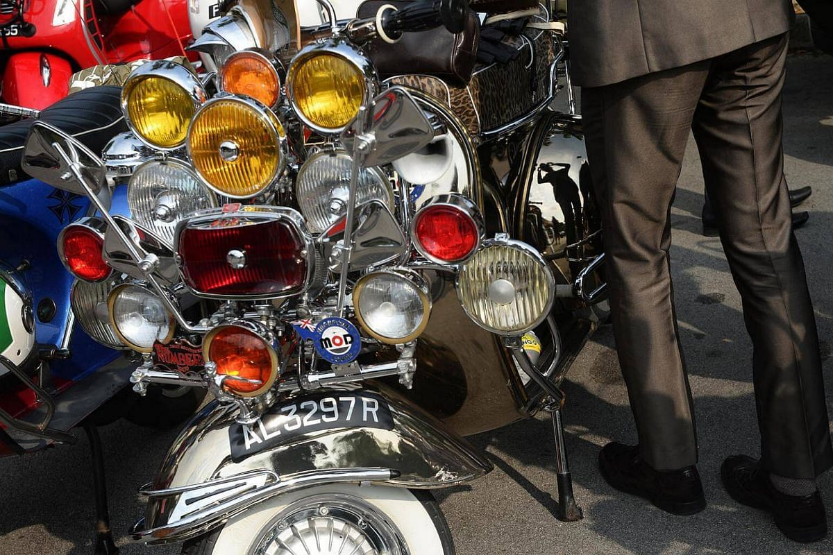 A participant of the 2016 Distinguished Gentlemen's Ride is reflected in the side panel of his vintage Vespa scooter at the Dempsey Road pitstop on Sept 25, 2016.