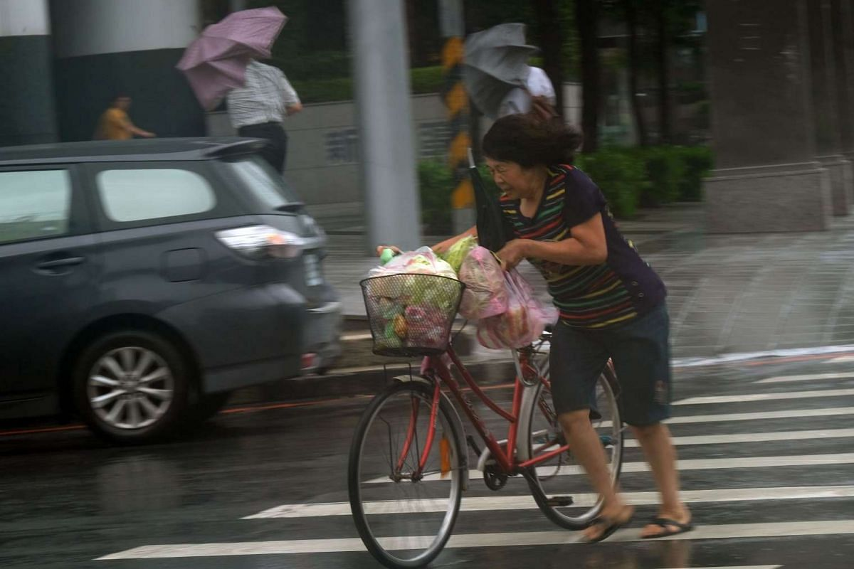 A woman pushes her bicycle during a storm in Panchiao district, New Taipei City, as Typhoon Megi hits eastern Taiwan on Sept 27, 2016.
