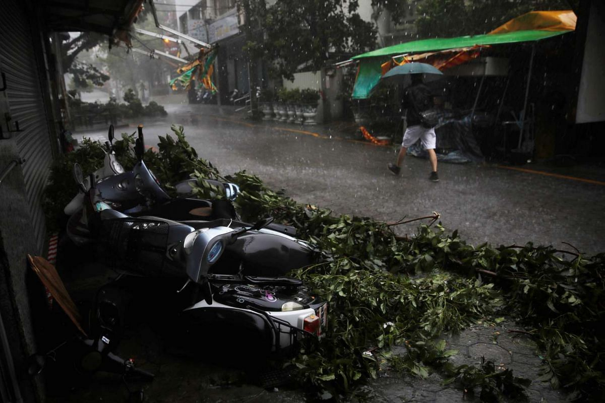 A man walks past motorcycles damaged by Typhoon Megi in Hualien county, eastern Taiwan on Sept 27, 2016.