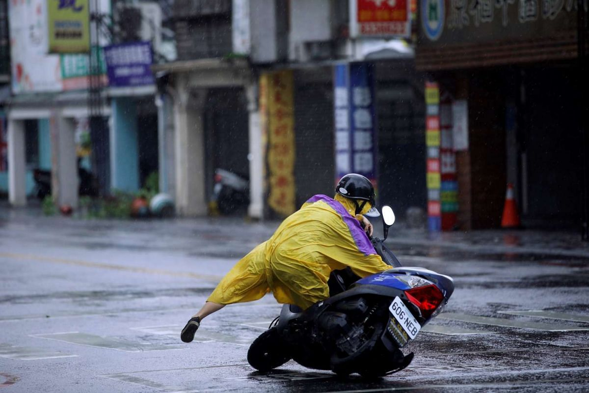 A motorcyclist falls along a road as Typhoon Megi hits Hualien county, eastern Taiwan on Sept 27, 2016.