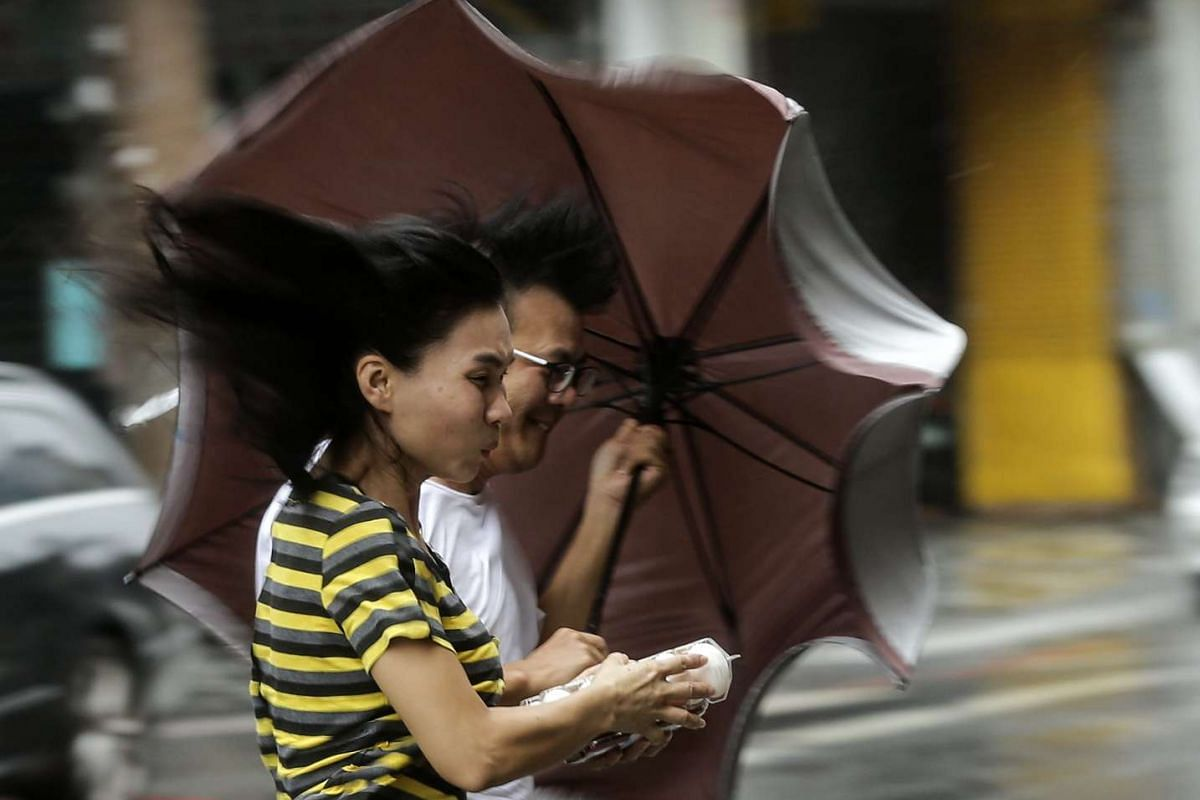 People brave to heavy rains and strong wind as typhoon Megi hits Hualien county, eastern Taiwan on Sept 27, 2016.