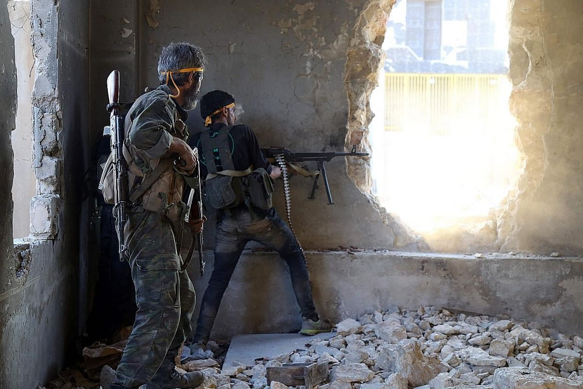 Rebel fighters firing towards positions of government forces in Ramussa on the south-western edges of Aleppo last month. The rebels are standing their ground and resisting government forces' scorched-earth tactics of siege and bombardment. Children b