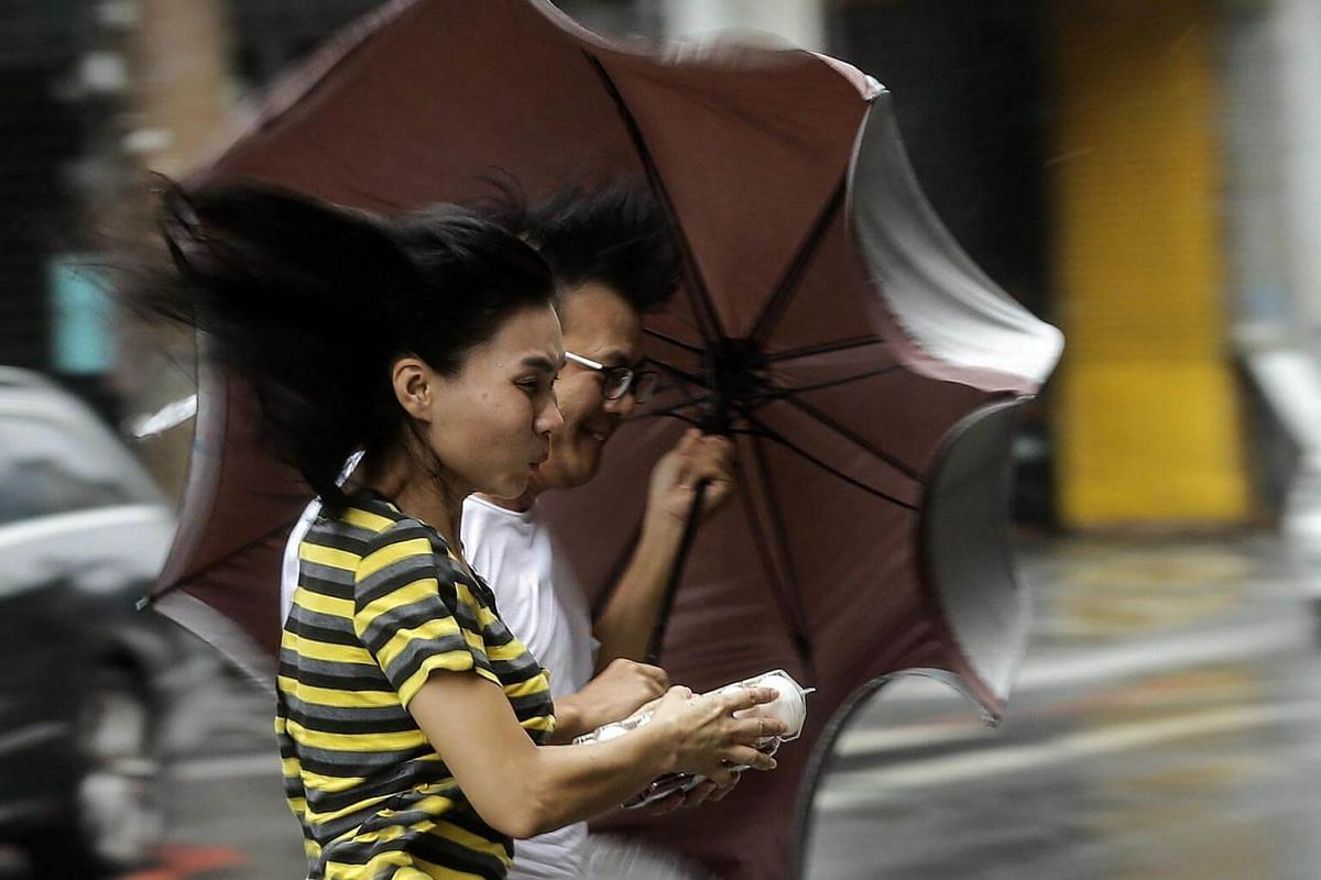 People brave heavy rains and strong wind as Typhoon Megi hits Hualien county, eastern Taiwan, on Sept 27, 2016.
