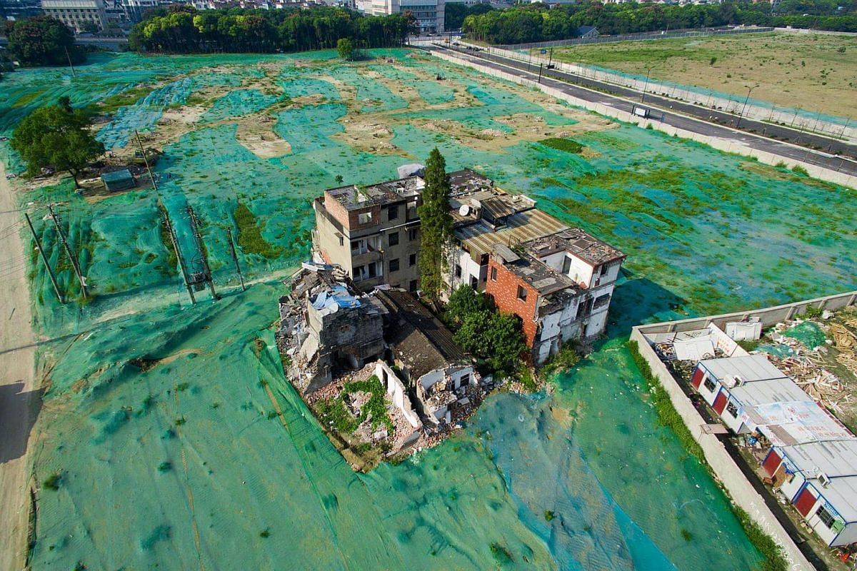 A nail house is seen in the middle of an area covered by a dust screen in Hangzhou, Zhejiang province, China, on Sept 26, 2016.
