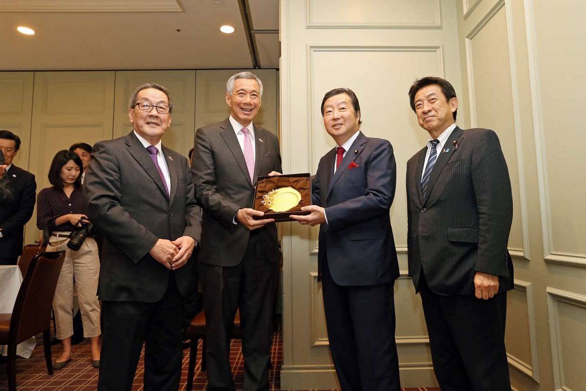 Prime Minister Lee Hsien Loong (second from left) presents a plaque to former Chairman of the JSPFL Mr Kenji Kosaka (second from right) for his contributions to relations between Singapore and Japan.