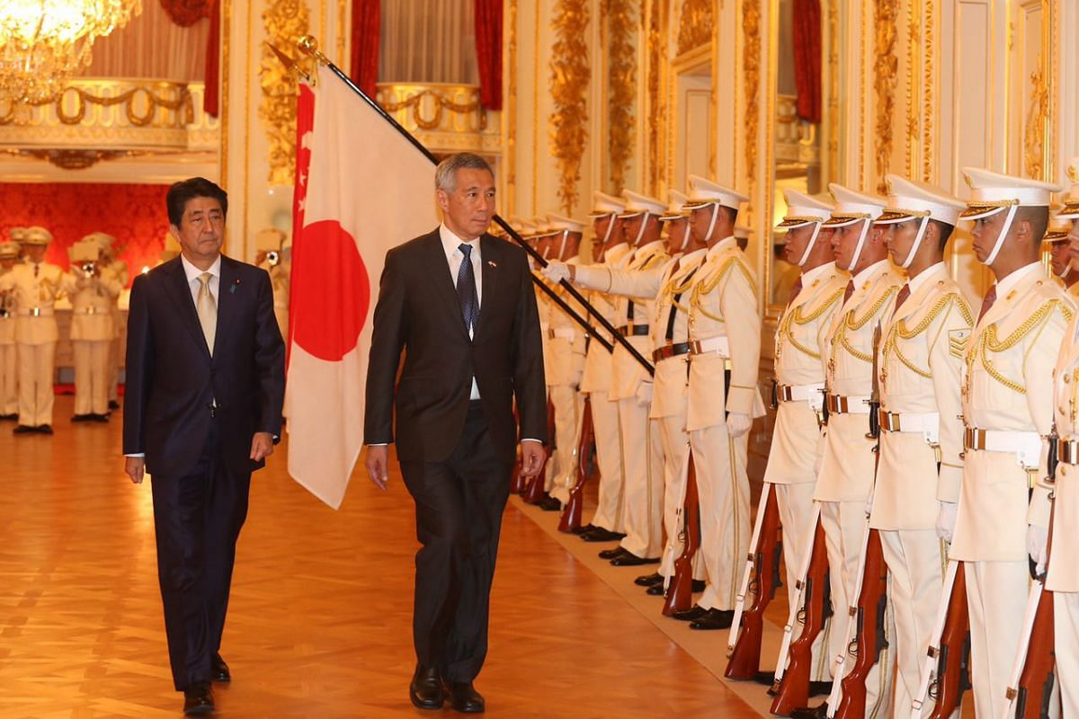 Prime Minister Lee Hsien Loong with his Japanese counterpart Shinzo Abe as they inspect the guard of honour at the Hagocomo no Ma, Akasaka State Guest House on Sept 28, 2016.