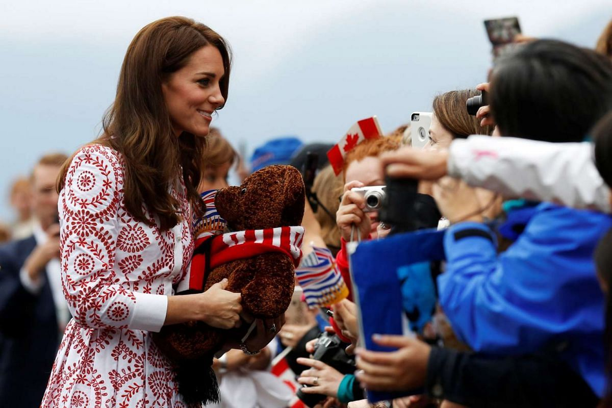Britain's Catherine, Duchess of Cambridge, carries a stuffed bear she received while greeting people at Jack Poole Plaza in Vancouver, British Columbia, Canada, on Sept 25.