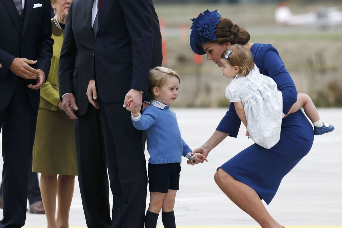 Catherine, Duchess of Cambridge tends to Prince George as she carries Princess Charlotte at Victoria Airport, Victoria, British Columbia, Canada on Sept 24.