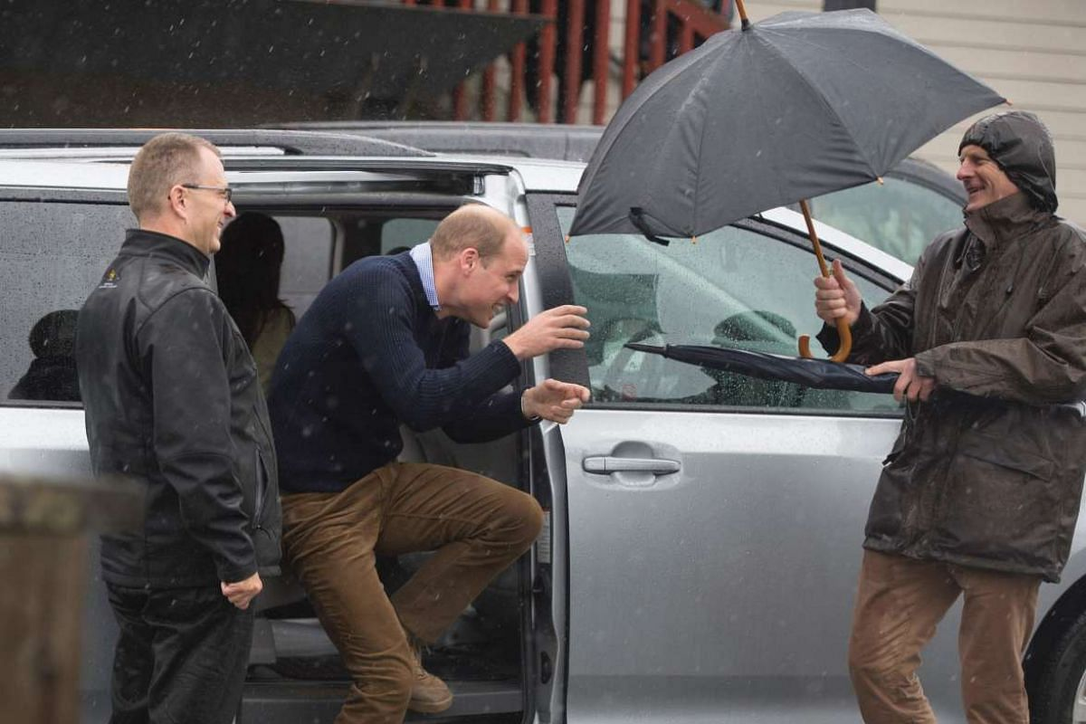 Prince William gets out of his car under heavy rain as he arrives in Bella Bella, British Columbia, on Sept 26.