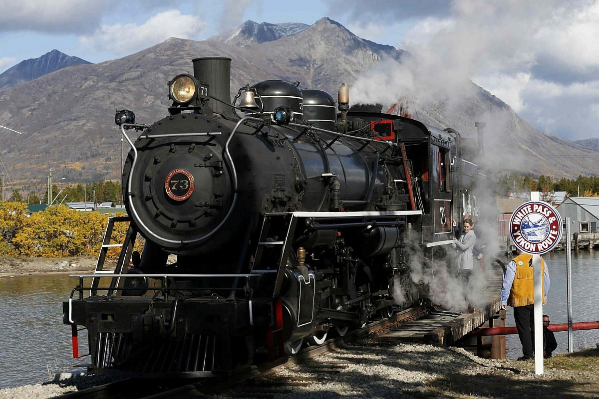 Britain's Catherine, Duchess of Cambridge, holds onto a railing after touring a steam locomotive in Carcross, Yukon, Canada, on Sept 28.