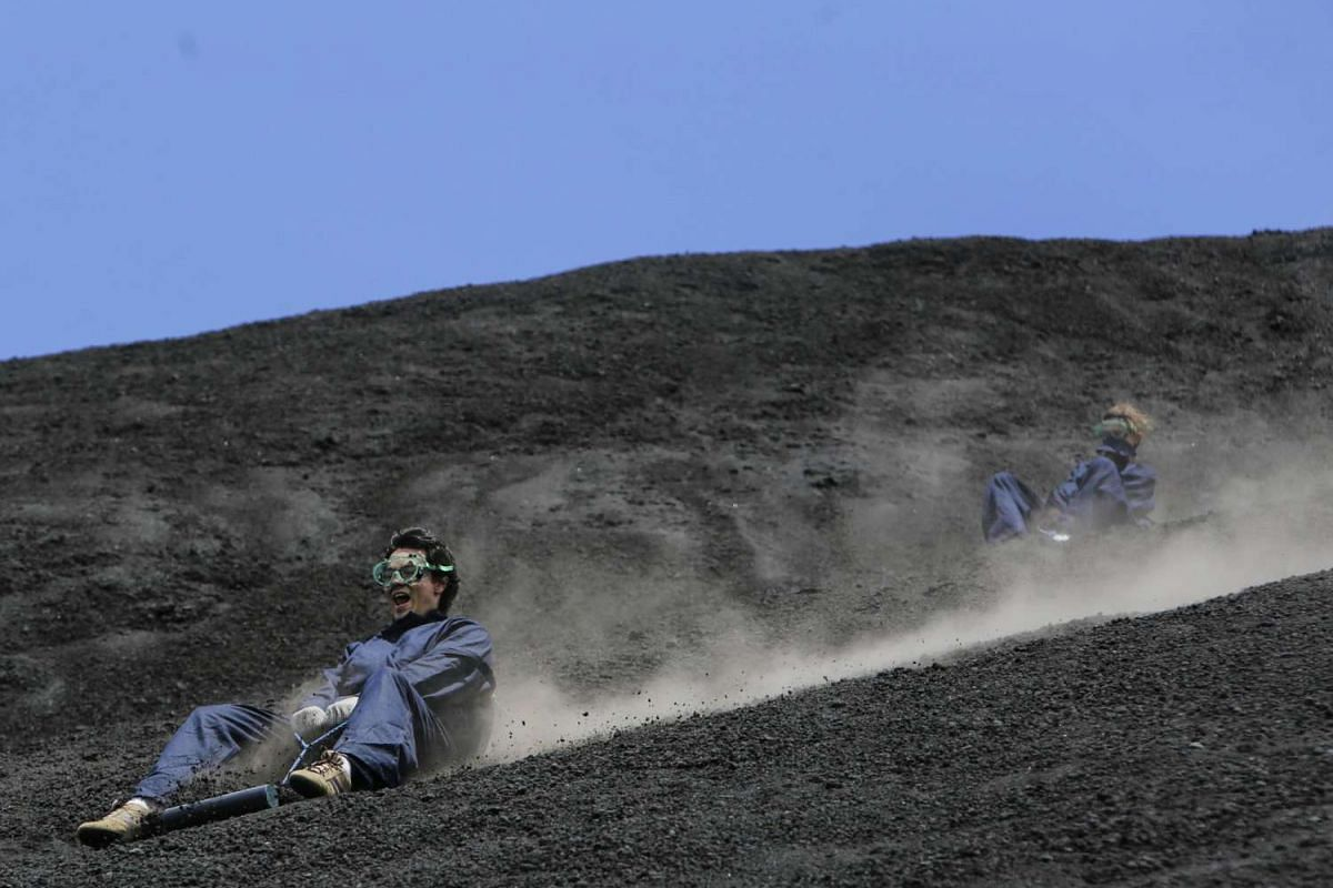 Tourists sandboard down the Cerro Negro volcano, in Leon, some 100km northwest from Managua on Sept 24, 2016.
