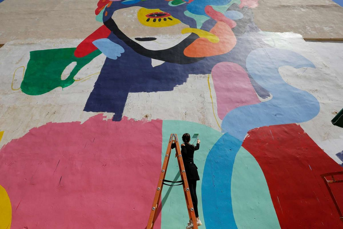 Brazilian artist Tarsila Schubert works on a mural about women empowerment on Sept 29. The project is part of the Open Art Museum, which aims to add colour to the city of Amman, Jordan.