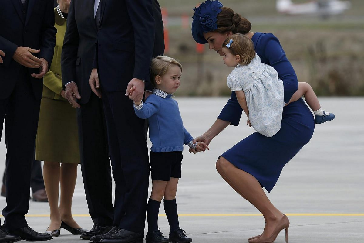 Catherine, Duchess of Cambridge holds the hand of her son Prince George while carrying Princess Charlotte as they arrive at the Victoria International Airport for the start of their eight day royal tour to Canada on Sept 24, 2016.