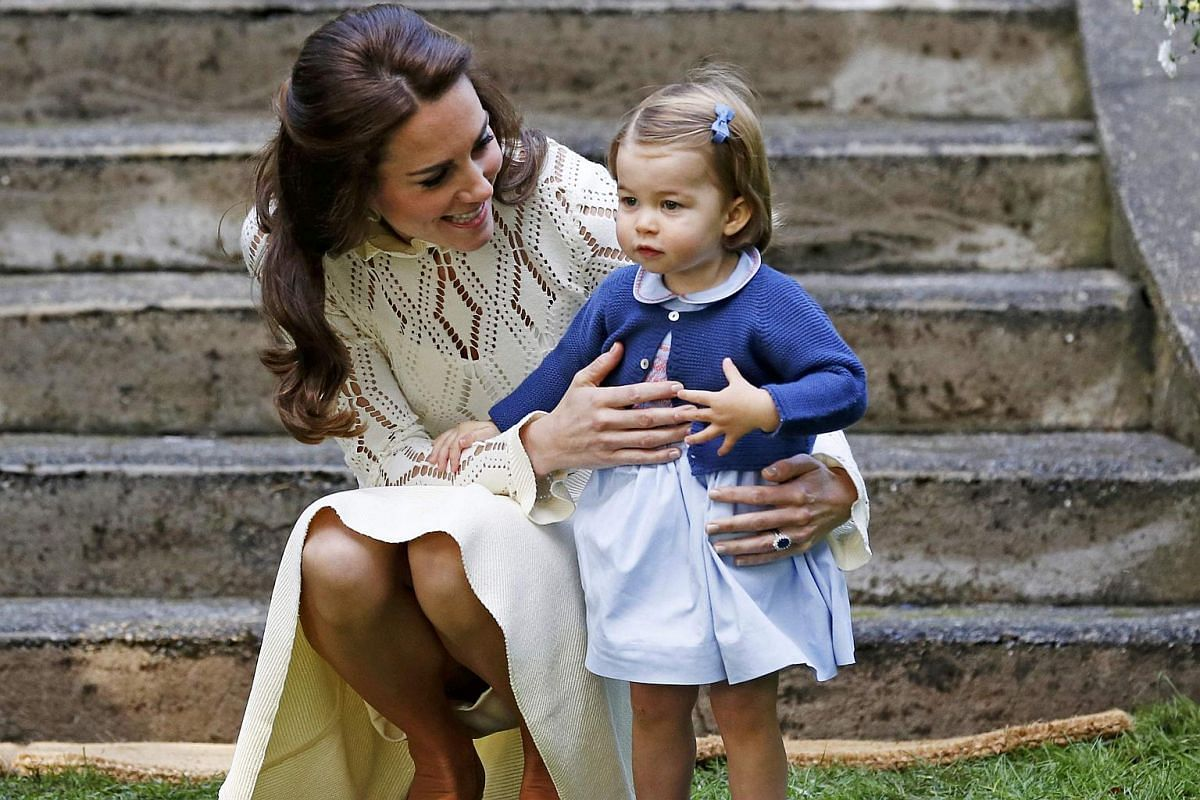 Catherine, Duchess of Cambridge, speaks to Princess Charlotte as they arrive at a children's party at Government House in Victoria, British Columbia on Sept 29, 2016.