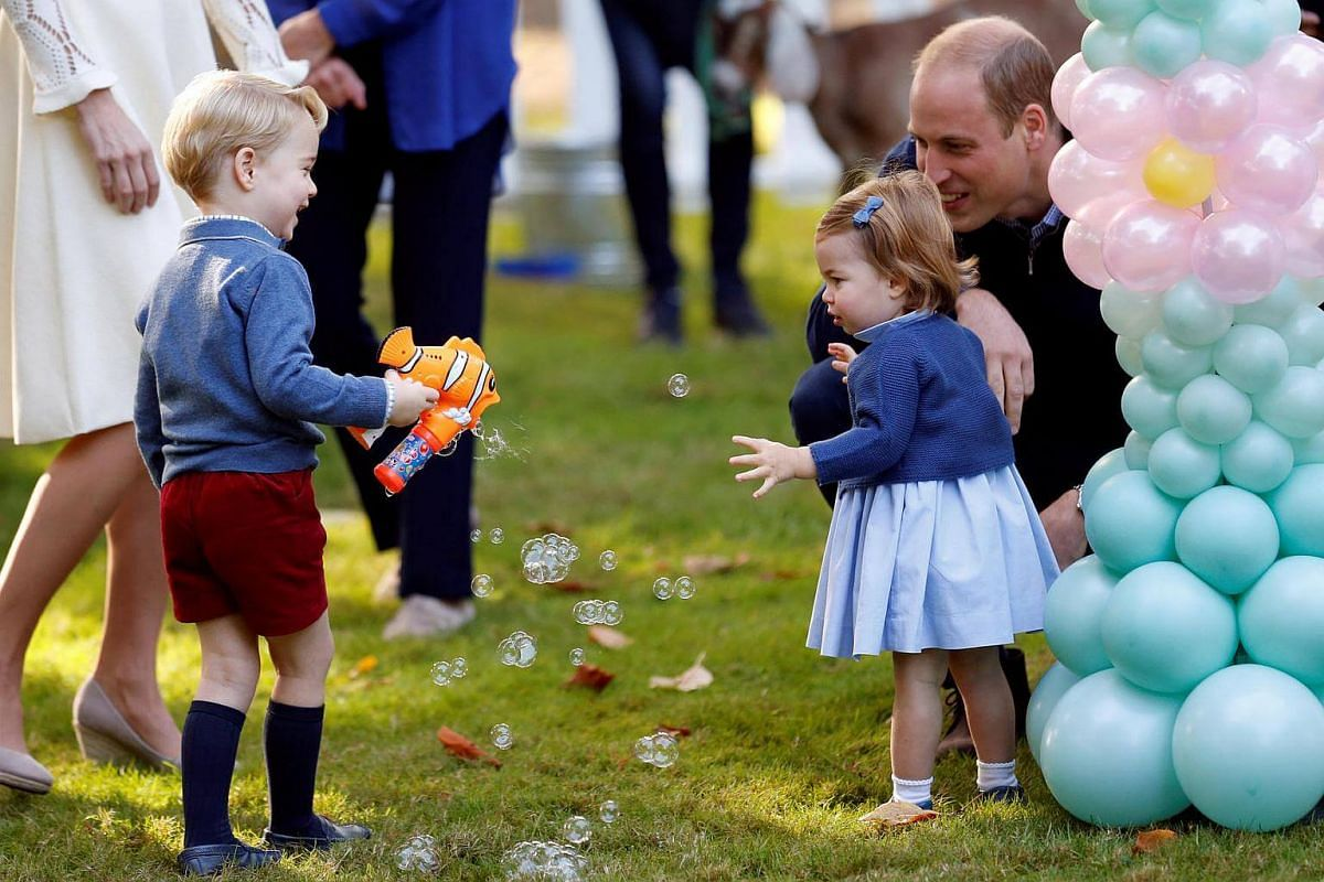 Britain's Prince William and Princess Charlotte look on as Prince George plays with a bubble gun at a children's party at Government House in Victoria, British Columbia, Canada, on Sept 29, 2016.