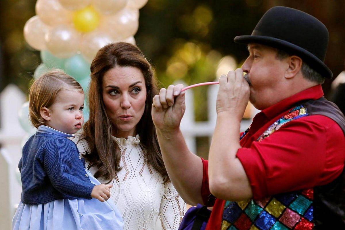 Britain's Catherine, Duchess of Cambridge, and Princess Charlotte watch a man inflate a balloon at a children's party at Government House in Victoria, British Columbia, Canada, on Sept 29, 2016.