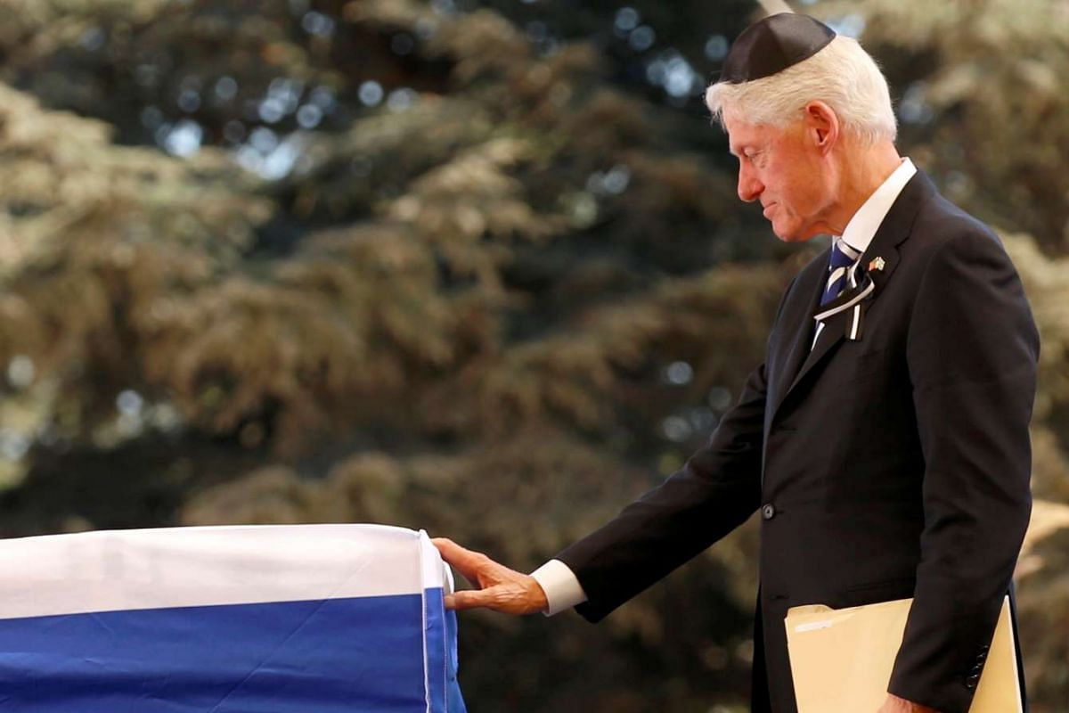 Former US President Bill Clinton touches the flag-draped coffin of former Israeli President Shimon Peres, after eulogising him during his funeral ceremony.