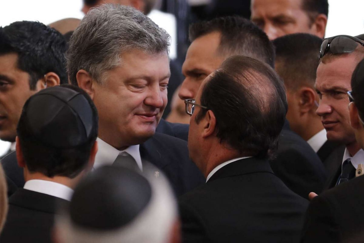 French President Francois Hollande (centre, right) and Ukranian President Petro Porochenko (centre, left) talk during the funeral.