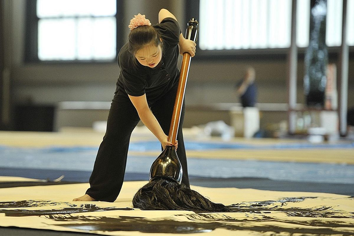 Shoko wielding her giant brush. She believes her father's spirit watches her from heaven when she does her calligraphy.