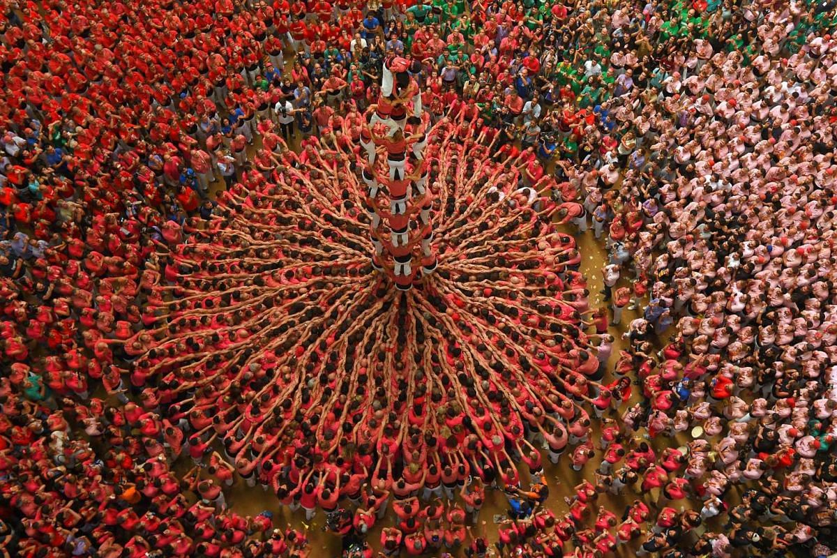 "Members of the Colla Vella dels Xiquets de Valls team form a ""castell"" (human tower) during the XXVI human towers competition in Tarragona on Oct 2, 2016."