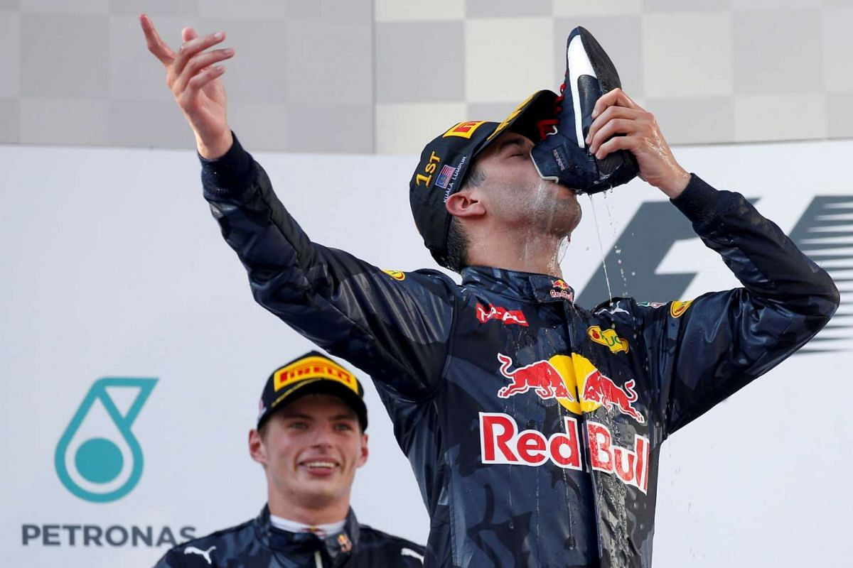 Red Bull's Daniel Ricciardo of Australia drinks from his shoe as he celebrates his Formula One Malaysia Grand Prix win on the podium in Sepang on Oct 2, 2016.