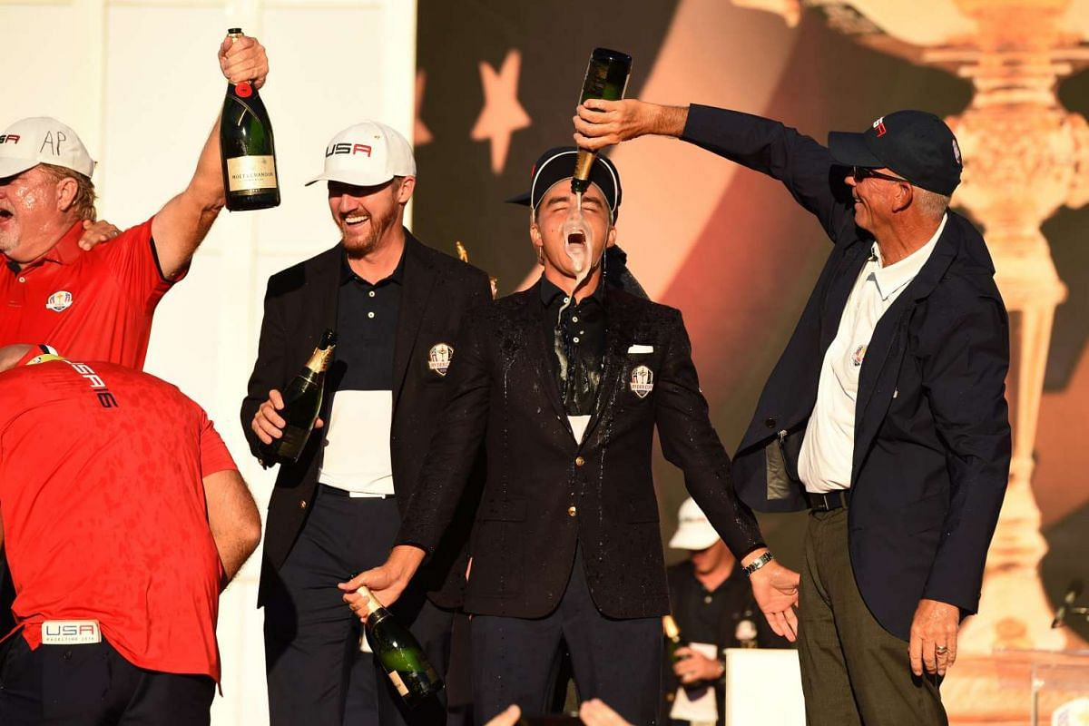 Team USA's Rickie Fowler gets champagne poured on him during the trophy ceremony after the Singles Matches during the 41st Ryder Cup at Hazeltine National Golf Course in Chaska, Minnesota, on Oct 2, 2016.