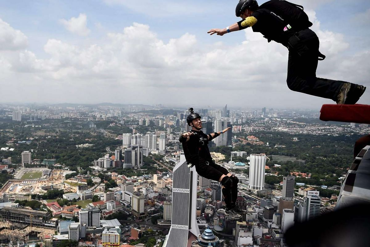 Base jumpers leap from the 300-metre high skydeck of Kuala Lumpur Tower on Oct 3, 2016 during the annual International KL Tower Base-Jump event.