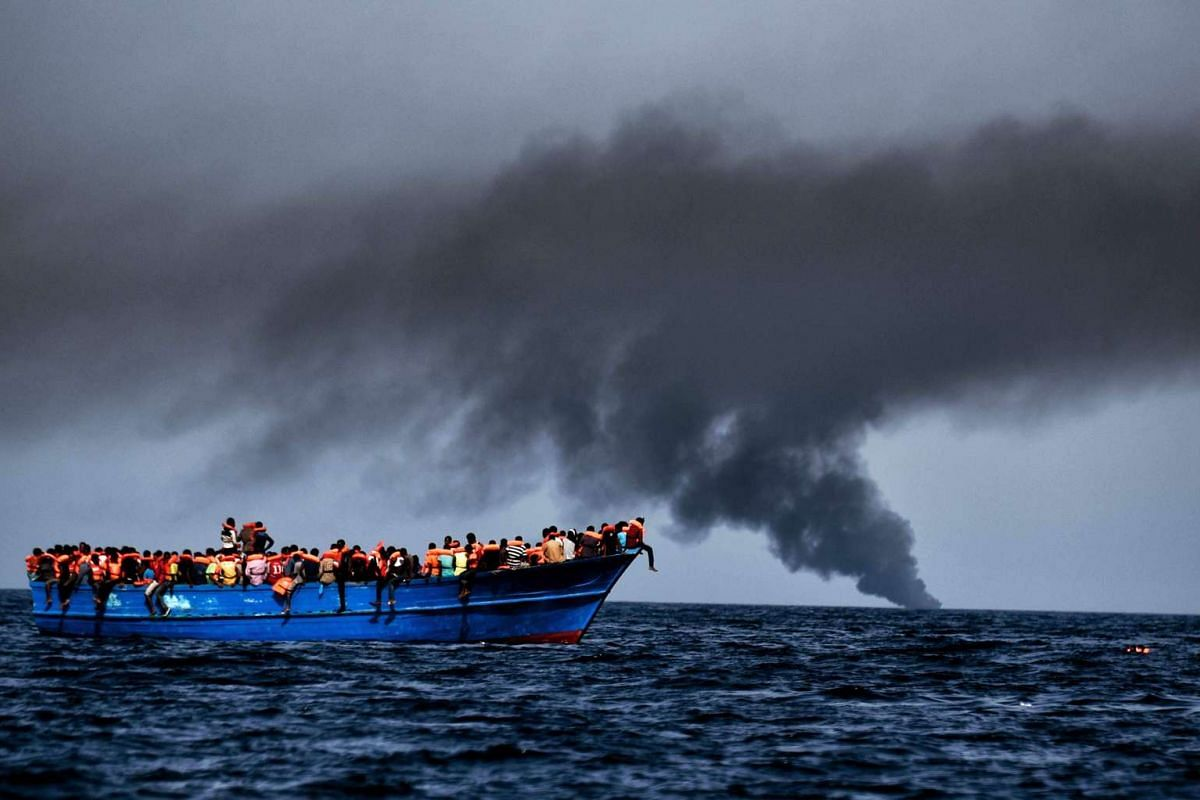 Migrants wait to be rescued as they drift at sunset in the Mediterranean Sea some 20 nautical miles north off the coast of Libya on Oct 3, 2016. PHOTO: AFP/HANDOUT/ARIS MESSINIS