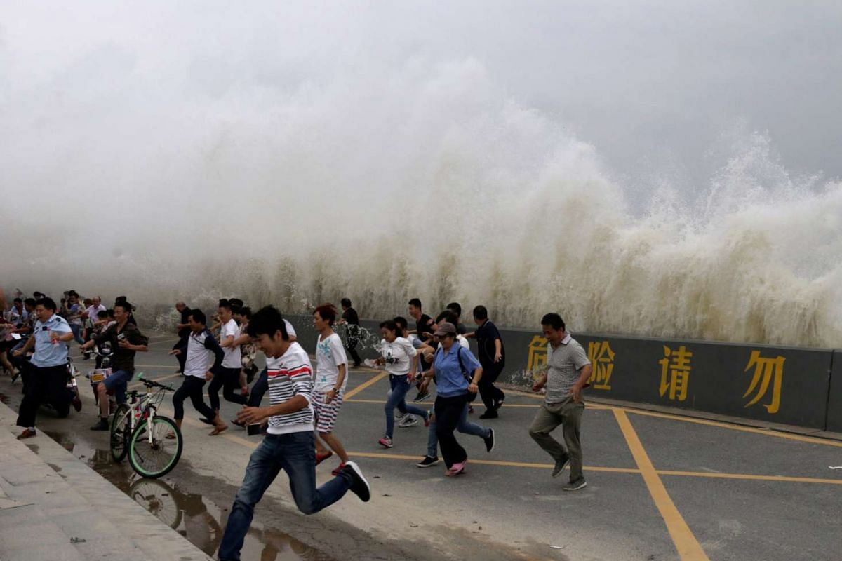 People run way from waves caused by a tidal bore which surged past a barrier on the banks of Qiantang River, in Hangzhou, Zhejiang province, China, Oct 3, 2016. PHOTO: REUTERS/HANDOUT/CHINA STRINGER NETWORK