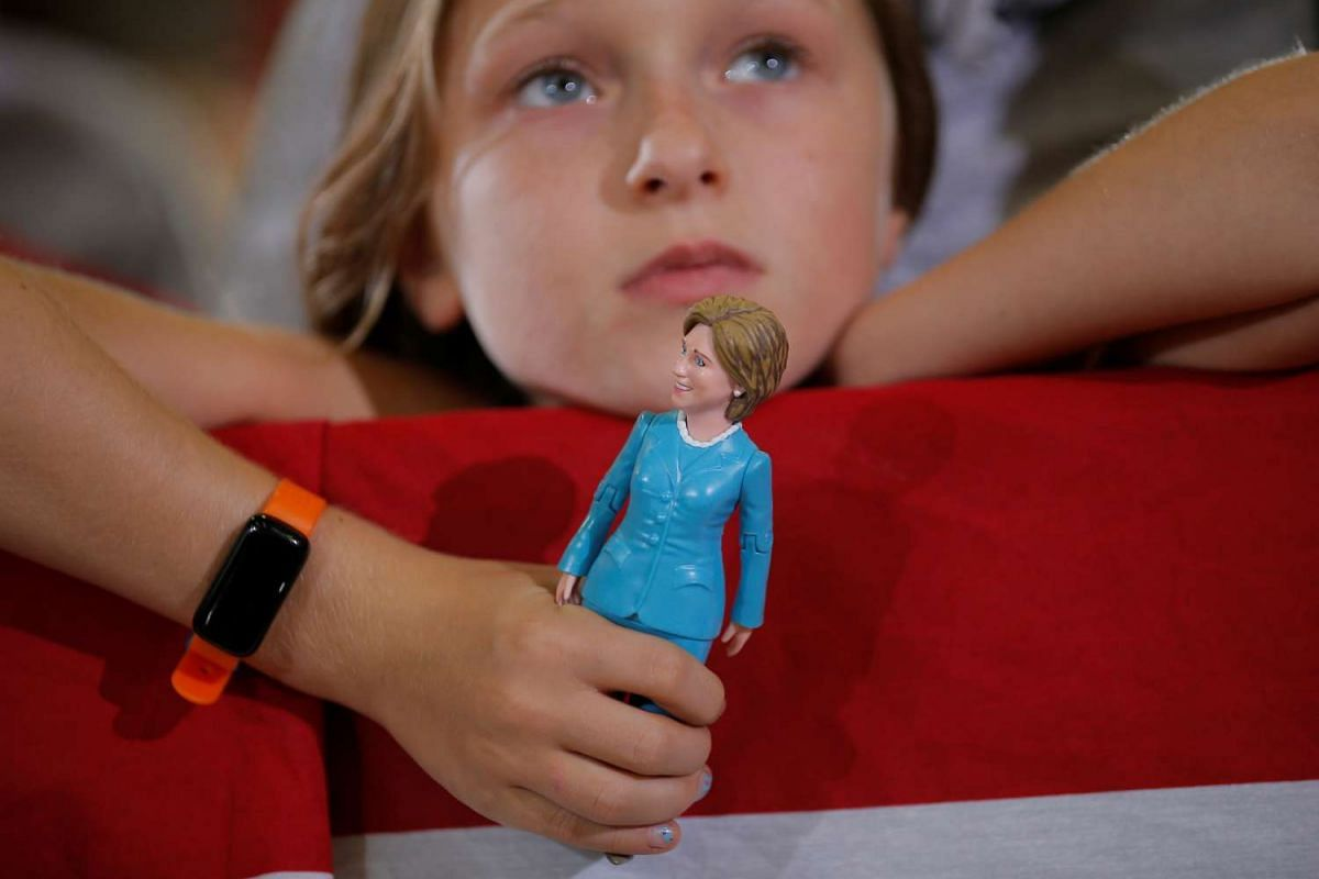 Nine-year-old Belle Shefrin holds a doll of US Democratic presidential nominee Hillary Clinton while listening to her speak at a campaign rally in Akron, Ohio, Oct 3, 2016. PHOTO: REUTERS