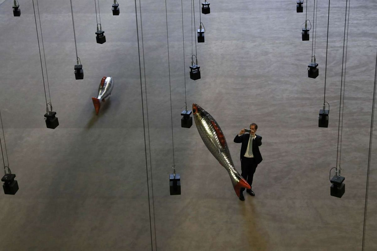 """A man takes a picture of the installation """"Anywhere"""" by French artist Philippe Parreno, in the Turbine Hall at Tate Modern in central London, Oct 3, 2016. PHOTO:REUTERS"""