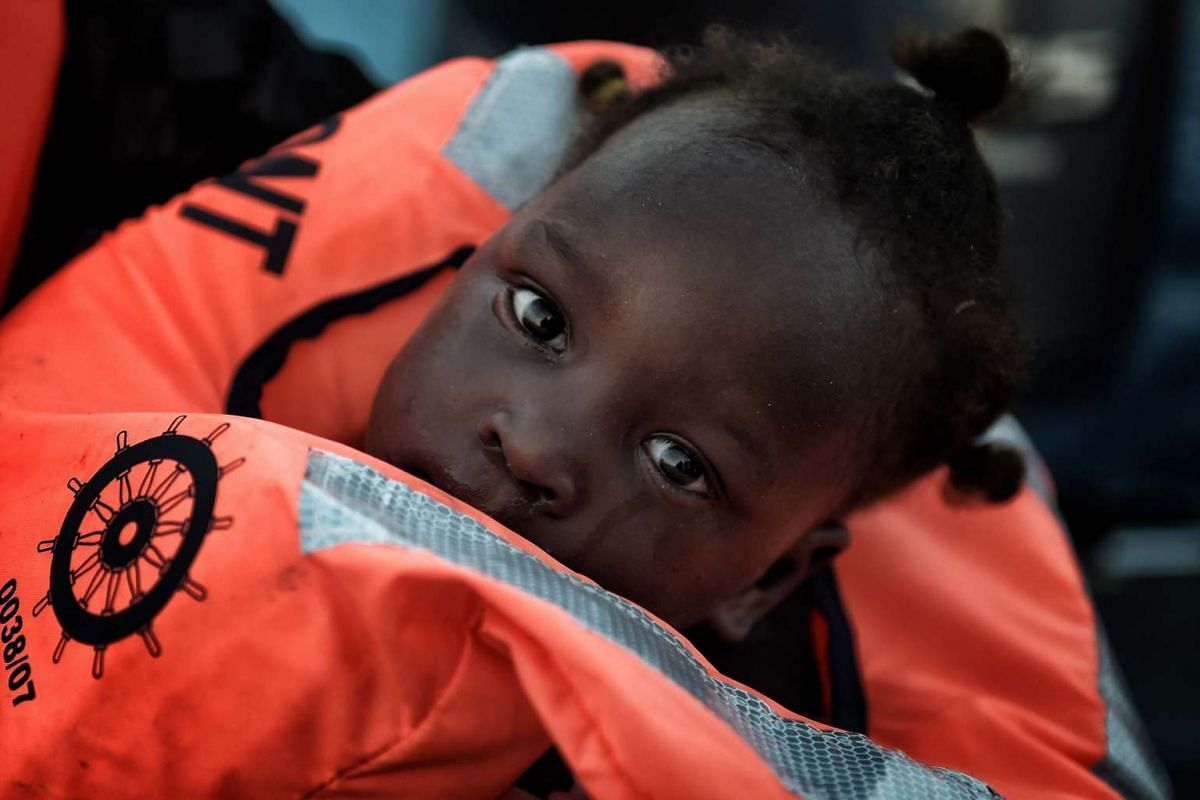 A child is rescued from a distressed vessel by a member of the Proactiva Open Arms NGO some 20 nautical miles north of Libya on Oct 3, 2016.