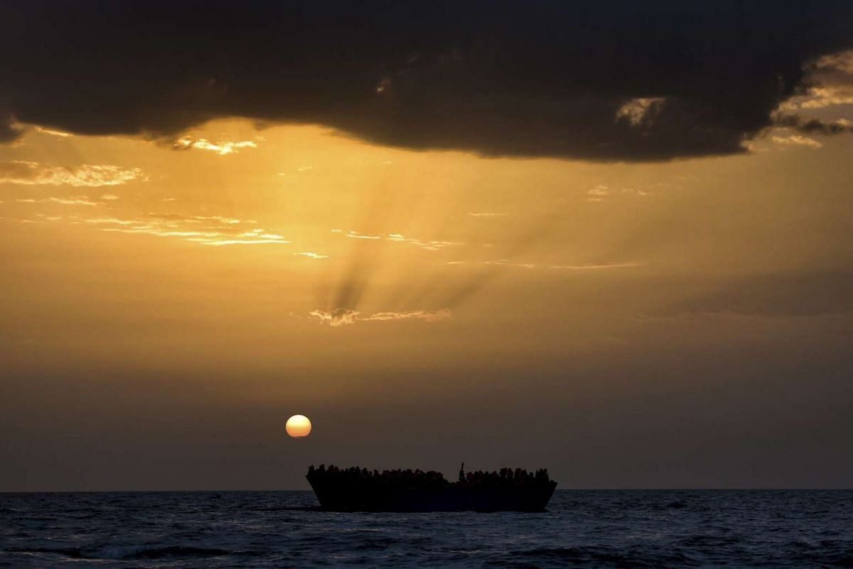 Migrants wait to be rescued as they drift at sunset in the Mediterranean Sea some 20 nautical miles north off the coast of Libya on Oct 3, 2016.