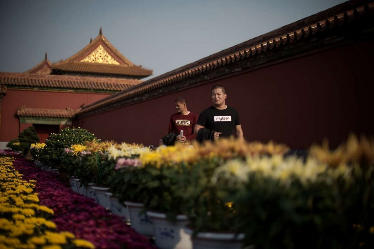 Two men look at a flower display inside the Forbidden City during China's Golden Week holiday in Beijing, on Sept 29, 2016.