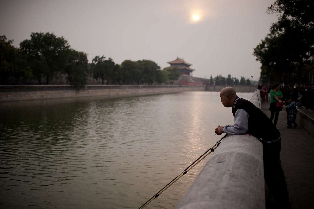 A man smokes a cigarette as he fishes in a canal outside the Forbidden City in Beijing on Sept 29, 2016.