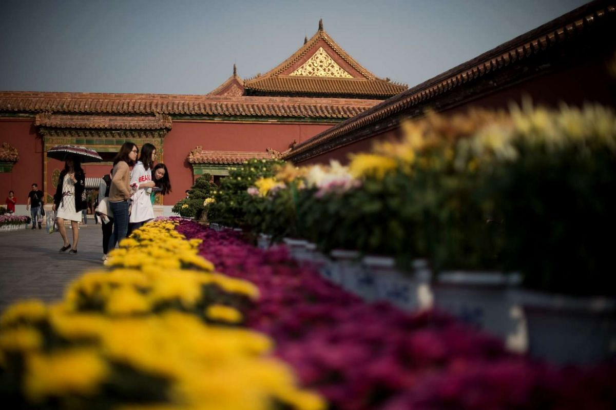 People look at a flower display inside the Forbidden City during China's Golden Week holiday in Beijing, on Sept 29, 2016.