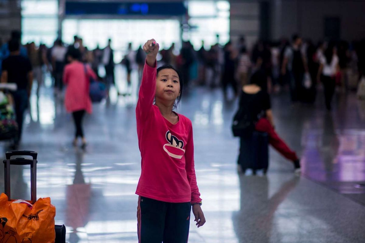 A young girl plays with a laser as she waits for her train during China's Golden Week holiday at the Hongqiao Translation in Shanghai, on Oct 1, 2016.