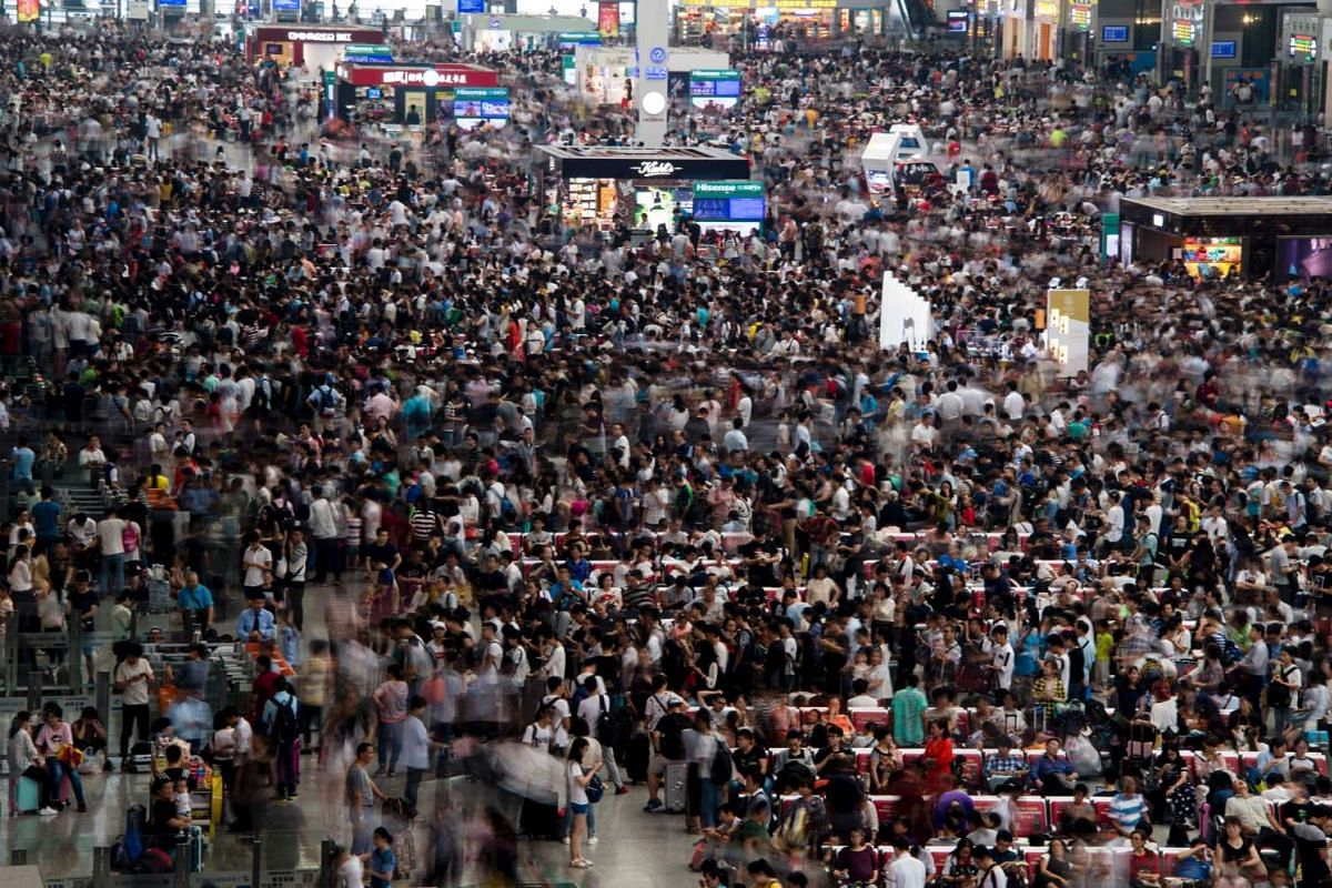 People wait for their trains during China's Golden Week holiday at the Hongqiao train station in Shanghai, on Oct 1, 2016