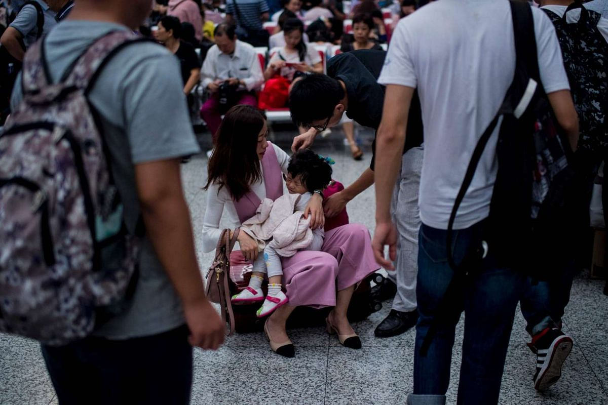 A family with a small child wait for their trains during China's Golden Week holiday at the Hongqiao train station in Shanghai, on Oct 1, 2016.