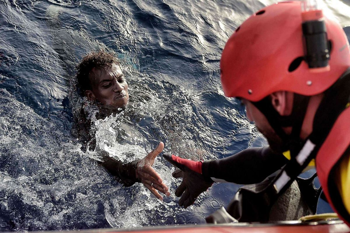 A migrant is rescued from the Mediterranean Sea by a member of the Proactiva Open Arms NGO some 20 nautical miles north of Libya on Oct 3, 2016.