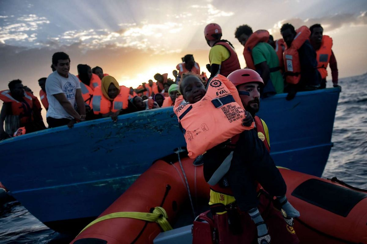 A child is rescued from a distressed vessel by a member of Proactiva Open Arms NGO some 20 nautical miles north of Libya on Oct 3, 2016.